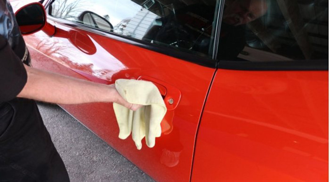 A person cleaning a car door handle with a cloth